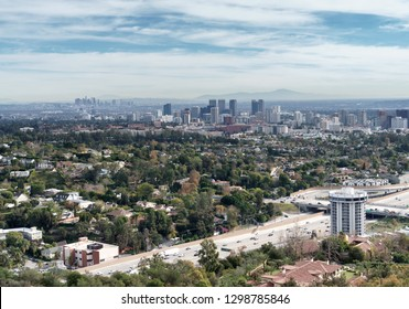 Aerial view of Los Angeles, California looking over the 405 freeway. Tall buildings and hills in background. Blue sky and clouds.