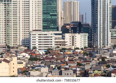 Aerial view of a low rise residential district, still organize like a village contrasting with modern condominium towers in the heart of Jakarta, Indonesia capital city.