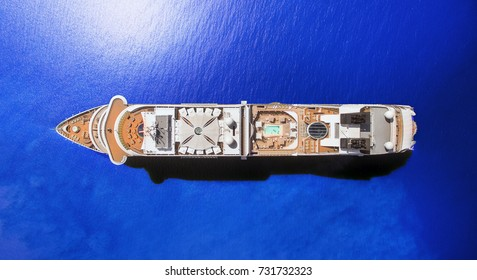 Aerial view of luxury cruise ship at blue ocean, top down view of swimming pool and deck