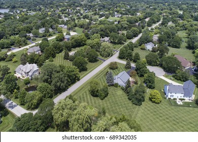 Aerial view of a luxury neighborhood with mature trees and large lots in a Chicago suburban neighborhood in summer.
