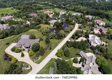 Aerial view of a luxury neighborhood with mature trees and a pond in a Chicago suburban neighborhood in summer.