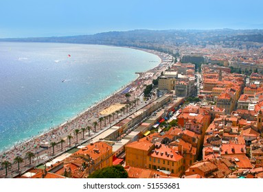 Aerial view of Luxury resort of French riviera. Beautiful panorama city of Nice in France. Sunny, summer day. Mediterranean sea, public beach, famous quay, palms and red tile roofs of Nice.