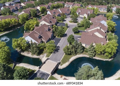 Aerial view of a luxury townhouse complex with a creek bordering the homes in a Chicago suburban neighborhood in summer.