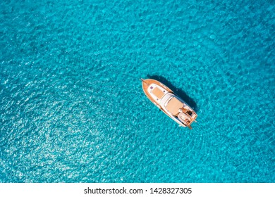 Aerial view of luxury yacht in transparent blue sea at sunny day in summer in Mallorca, Spain. Colorful landscape with boat, bay, clear azure water. Top view from air. Travel. Seascape with motorboat