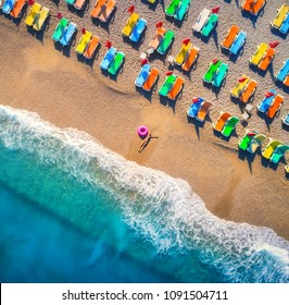 Aerial view of lying woman with swim ring in the sea in Oludeniz, Turkey. Summer scene with young girl, blue water, waves and sandy beach with colorful chaise-lounges at sunset. Top view. Travel