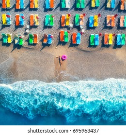 Aerial view of lying woman with swim ring in the sea in Oludeniz, Turkey. Summer seascape with girl, azure water, waves and sandy beach with colorful chaise-lounges at sunrise. Top view from drone