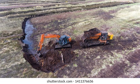Aerial view of machinery harvesting peat bog during early summer in rural Ireland