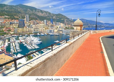 Aerial view to the main harbor and distant buildings of Monte Carlo seen from the medieval walls of Monaco-ville, Monaco