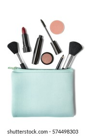 Aerial view of make up products spilling out of a pastel blue cosmetics bag, isolated on a white background