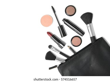 Aerial view of make up products spilling out of a black leather cosmetics bag, isolated on a white background with blank space at side