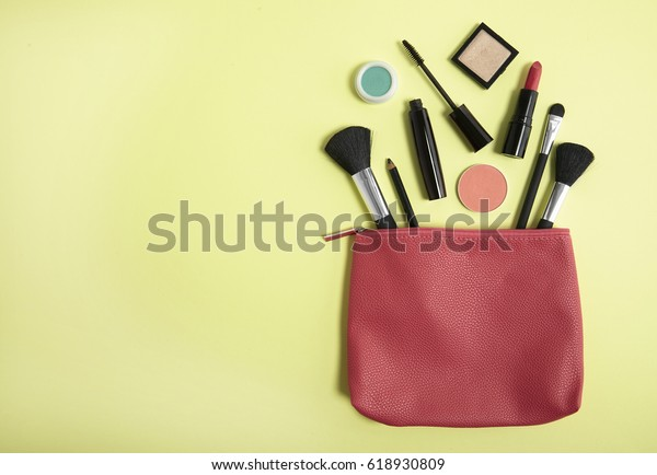 Aerial view of make up products spilling out of a pink leather cosmetics bag on to a pastel yellow background, with blank space at side