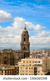 An aerial view of Malaga's skyline featuring Malaga Cathedral, with a blue cloudy sky as a backdrop.  Image has copy space.