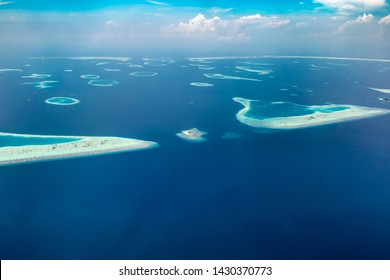 Aerial view of Maldives islands and atolls. Maldives tourism and travel background. Amazing blue sea, coral reef and atoll drone view. Beautiful nature landscape, seascape, exotic destination