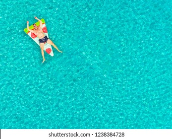 Aerial view of man floating on inflatable pizza shaped mattress