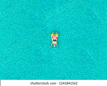 Aerial view of man floating on inflatable pizza shaped mattress, relaxing on transparent sea.