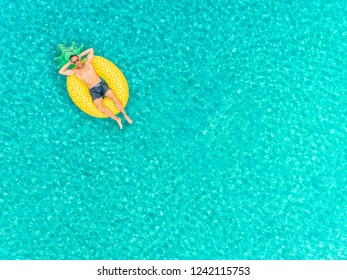 Aerial view of man floating on inflatable pineapple mattress on transparent sea.