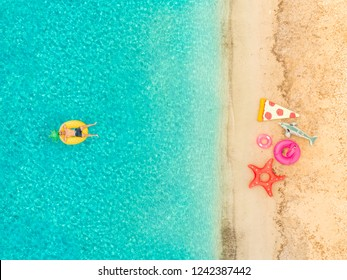 Aerial view of man floating on inflatable pineapple mattress by sandy beach and inflatable rings.
