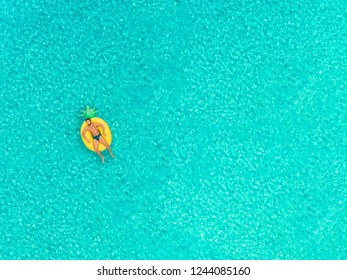 Aerial view of man floating on inflatable pineapple shaped mattress, sunbathing.