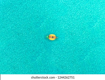 Aerial view of man floating on inflatable pineapple shaped mattress in transparent sea.