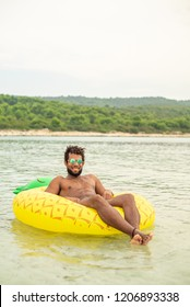 Aerial view of man with inflatable pineapple shaped mattress, smiling.