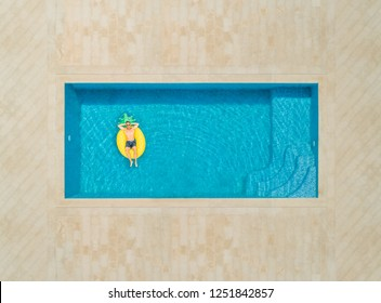 Aerial view of man on pineapple shaped inflatable mattress in swimming pool.