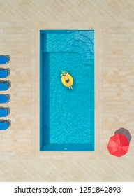 Aerial view of man on pineapple shaped inflatable mattress in swimming pool surrounded by deck chairs and parasol.