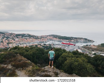 Aerial view of a man stands with his back to the viewer on the top of a mountain. In the background, a city by the sea, a cruise ship, many small houses. Goal achievement, independence and success.