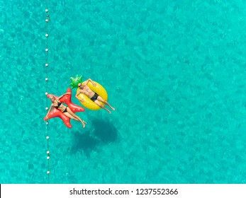 Aerial view of man and woman floating by string buoy on inflatable mattresses in clear blue sea.