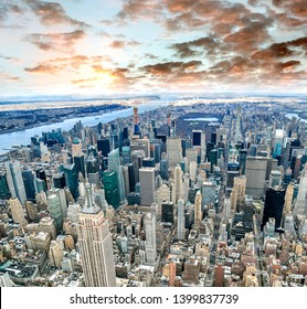 Aerial view of Manhattan skyline from the sky on a cloudy day, New York City at sunset.
