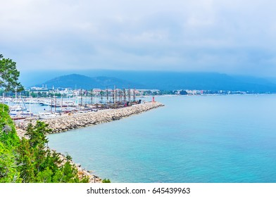 Aerial view of Marina with yachts and ships and the coast of Kemer with foggy Taurus mountains on the background, Turkey.