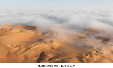 Aerial view of a massive sand dune surrounded by winter morning fog cloud in Empty Quarter. Liwa desert, Abu Dhabi, United Arab Emirates.