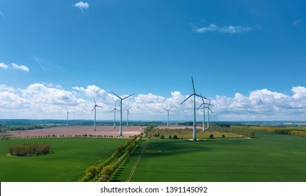 aerial view of meadows and wind turbines in the background - blue sky