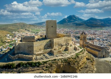Vista aérea del Castillo medieval de Alcaudete en Andalucía España con donjón, altas paredes de piedra y resquicios al lado de la iglesia de la ciudad