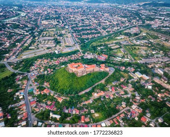Aerial view of medieval castle Palanok, Mukachevo (Munkacs), Transcarpathia (Zakarpattia), Ukraine. Summer landscape with old architecture, green trees and town, outdoor travel background