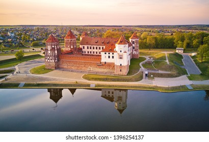Aerial view of Medieval Mir castle complex at spring sunset. Famous landmark, UNESCO world heritage. Drone panorama of Mirsky zamok, Belarus