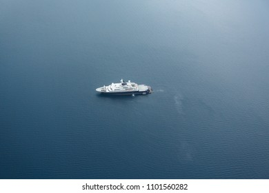 Aerial view of mega yacht silhouetted against blue water in middle of the wide Pacific ocean