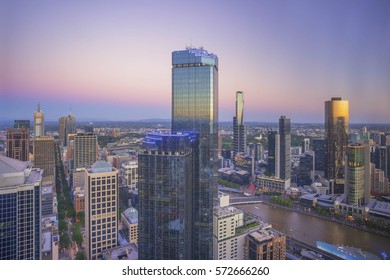 An aerial view of Melbourne cityscape including Yarra River and Victoria Harbour in the distance during sunset with beautiful majestic blue hour sky