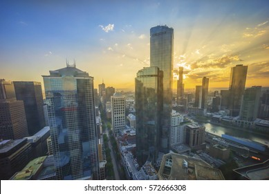 An aerial view of Melbourne cityscape including Yarra River and Victoria Harbour in the distance during sunrise with beautiful sun ray bursting through clouds.
