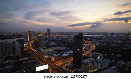 Aerial view of metropolitan freeway interchange which Expressway, Highway, Motorway, Tollway,  sunset  on roof in Bangkok, Thailand.