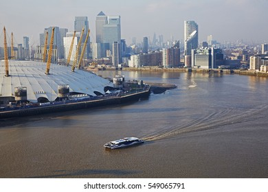 Aerial view of Millennium Dome (02 Arena) and financial district of Canary Wharf with London Ferry on River Thames