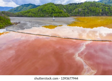 Aerial view of mining settling basin and lime supply. Colorful red polluted mine water from copper open pit excavation in Geamana, Rosia Montana, Romania by drone