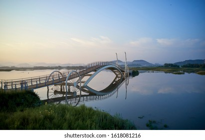 Aerial view of the Misaeng Bridge, Siheung-si, Gyeonggi-do, Korea - August 3, 2019: A bicycle wheel-shaped bridge is laid on the high tide sea water.