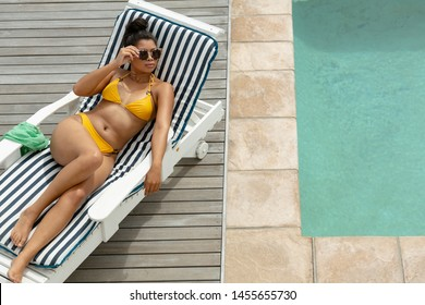 Aerial view of mixed-race woman in bikini sunglasses relaxing on a sun lounger near swimming pool at the backyard of home. Summer fun at home by the swimming pool