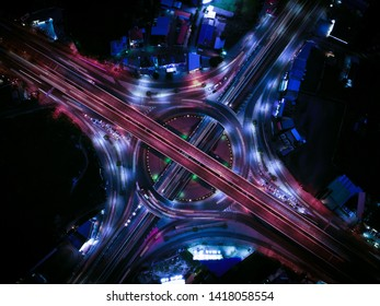 Aerial view of Modern city and smart transportation with Expressway, Road and Roundabout, busy highway traffic night time. Important infrastructure.