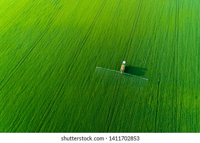 Aerial view of modern farm machine sprayer on green field. Modern technology of agriculture