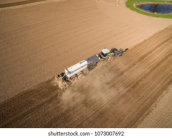 Aerial view of modern Tractor with liquid manure on the agricultural field - prepares it for sowing -  set of equipment for making liquid fertilizer into the soil in the agricultural field