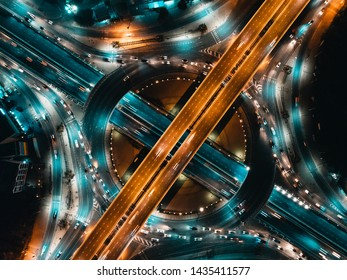 Aerial view of Modern transportation with Expressway, Road and Roundabout, busy highway traffic night time. Important infrastructure.