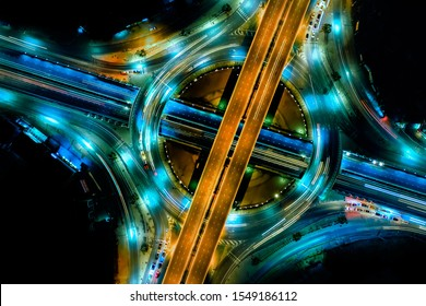 Aerial view of Modern transportation with Expressway, Road and Roundabout, multilevel junction highway-Top view. Car movement at night Important infrastructure.