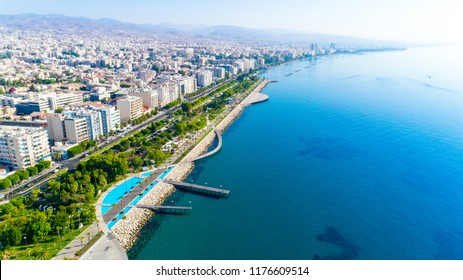 Aerial view of Molos Promenade park on coast of Limassol city centre,Cyprus. Bird's eye view of the jetty, beachfront walk path, palm trees, Mediterranean sea, piers, urban skyline and port from above