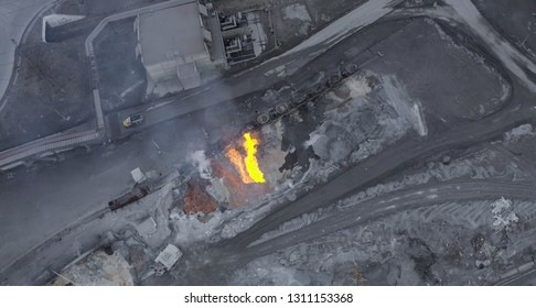 Aerial view. The molten slag is poured from a crucible mounted on a railway platform. A stream of molten slag.
